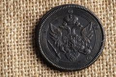 Auf Segeltuch ist Gewebe eine alte russische Münze mit einem doppelköpfigen Adler, eine Kupfermünze Stockfotografie