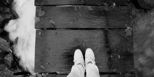 Auf seinen Füßen beschuht unter der Brücke das Wasser Stockfoto