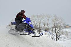 Auf Snowmobile springt der Mitfahrer hinunter den Berg Lizenzfreies Stockbild