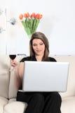 Auf Sofa mit Computer- und Weinglas Stockfoto