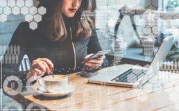 Auf Tabelle ist Laptop Mädchengraseninternet, plaudernd, blogging Weibliches haltenes Telefon und Schauen auf seinem Schirm Lizenzfreie Stockfotos