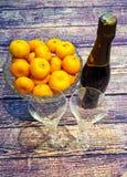 auf Tangerinen eines Holztischs in einem Kristallvase, in den Weingläsern und in einer Flasche Champagner Stockfoto