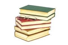 Auf Weiß ist eine Oberfläche ein Stapel von Büchern und von Lesebrille Lizenzfreie Stockfotografie