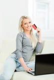 auf weißem background Schönes blondes Mädchen mit einer Kreditkarte Stockfotografie