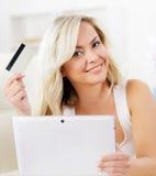 auf weißem background Schönes blondes Mädchen mit einer Kreditkarte Stockbild