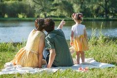 Auf weißem Plaid sitzen Sie erzieht zurück Betrachten Sie den Teich Vati zeigt einen Finger in den Abstand Lizenzfreies Stockfoto