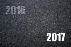 Auf Wiedersehen altes Jahr 2016 und guten Rutsch ins Neue Jahr 2017 auf Asphalt Textur Lizenzfreies Stockbild