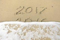 Auf Wiedersehen 2016 hallo 2017 Aufschrift geschrieben in den Strandsand Stockbild