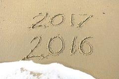 Auf Wiedersehen 2016 hallo 2017 Aufschrift geschrieben in den Strandsand Stockfotografie