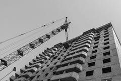 Aufbau in Bewegung Mehrstöckiges Wohngebäude Haus und Kran einfarbiges Bild Lizenzfreies Stockfoto