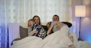 Aufbau mit Schrauben und Muttern Die Ehemann- und Fraulüge auf dem Bett und die Programme im dem Fernsehen mit der Fernbedienung  stock footage