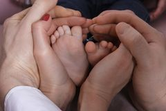 Aufbau mit Schrauben und Muttern Eltern umarmen ihre Baby ` s Beine Lizenzfreies Stockbild