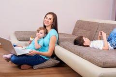 Aufbau mit Schrauben und Muttern Glückliche Familie mit Laptop, Telefon auf dem Boden in t stockfoto