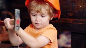 Aufbau mit Schrauben und Muttern Kinderjunge in der Werkstatt Kind, das Klotznagel lernt Junge, der mit Werkzeugen arbeitet Besch stock video footage