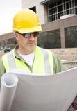 Aufbau-Vorarbeiter, der Lichtpausen betrachtet Lizenzfreies Stockfoto