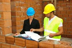 Aufbauarbeitskräfte, die auf Hausplänen schauen Stockfotos