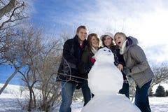 Aufbauen eines Schneemanns mit Freunden Stockfotografie