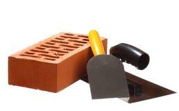 Aufbauhilfsmittel und ein Ziegelstein Stockfotografie