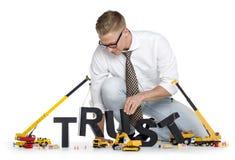 Aufbauvertrauen: Geschäftsmanngebäude Vertrauenwort. Lizenzfreie Stockfotos