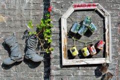Aufbereitete Stiefel und Dosen benutzt als Pflanzer lizenzfreies stockfoto