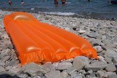 Aufblasbare Seematratze auf einem Steinstrand stockfotografie