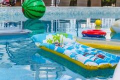 Aufblasbare Wasseraktivitäten, Bälle, Matratzen, Kreise, Rohre schwimmen auf das Wasser im Pool lizenzfreies stockbild
