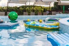 Aufblasbare Wasseraktivit?ten, B?lle, Matratzen, Kreise, Rohre schwimmen auf das Wasser im Pool lizenzfreies stockfoto