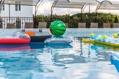 Aufblasbare Wasseraktivit?ten, B?lle, Matratzen, Kreise, Rohre schwimmen auf das Wasser im Pool lizenzfreie stockfotos
