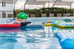 Aufblasbare Wasseraktivit?ten, B?lle, Matratzen, Kreise, Rohre schwimmen auf das Wasser im Pool lizenzfreies stockbild