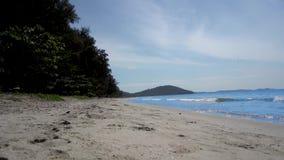 Aufblasbarer Rettungsringverkäufer geht entlang einen schneeweißen Strand mit blauem Wasser stock footage