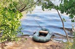 Aufblasbares Boot auf der Bank des Sees Rod und anderes Fischen Stockbilder