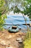Aufblasbares Boot auf der Bank des Sees Rod und anderes Fischen Lizenzfreies Stockfoto