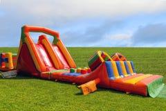 Aufblasbares Kind-` s Dia auf dem grünen Gras Lizenzfreies Stockfoto