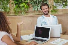 Aufeinander einwirkende Führungskräfte bei der Anwendung des Laptops Lizenzfreie Stockbilder
