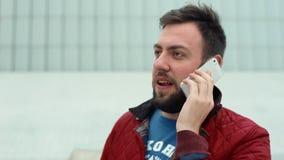 Aufenthalt des gutaussehenden Mannes und Unterhaltung an einem Handy stock footage
