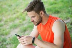 Aufenthalt on-line-- und verfügbar Sportlertext sms auf Frischluft Mann entspannen sich mit Smartphone auf grünem Gras Sommertäti Stockfotografie