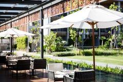 Aufenthaltsraum und Restaurant im Freien nahe durch die Pool- und Gartenansicht lizenzfreies stockfoto