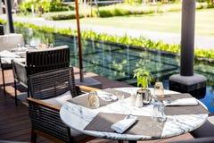 Aufenthaltsraum und Restaurant im Freien nahe durch die Pool- und Gartenansicht stockfotos