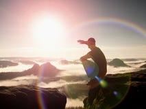 aufflackern Linsendefekt, Reflexionen Mann in der Sportkleidung sitzt auf dem Rand der Klippe und schaut zum nebelhaften Tal stockfotos