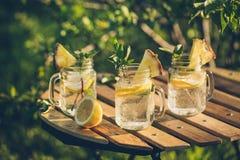 Auffrischungsgekühltes Zitronenwasser auf dem Gartentisch Stockfotografie