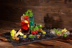 Auffrischungsgetränke mit Minze, Kalk, Eis, Beeren und Carambola auf dem schwarzen Schreibtisch Köstliche Sommer-Cocktails Kopier Lizenzfreie Stockfotografie