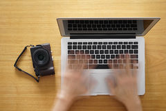 Aufgabe von Bildern online durch Laptop lizenzfreie stockbilder