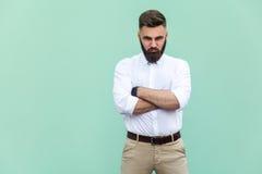 Aufgebrachter Mann, wenn die Arme, über hellgrünem Hintergrund gefaltet sind, in der Atelieraufnahme lizenzfreie stockfotos
