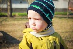 Aufgebrachter, trauriger kleiner Junge, der im Garten auf dem Playgroun sitzt Lizenzfreies Stockfoto