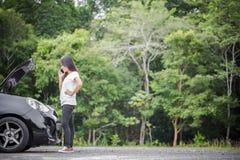 Aufgegliedertes Auto und asiatische Frau, die Automechaniker anruft lizenzfreies stockbild