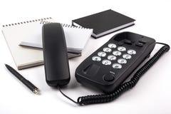 Aufgehobenes Telefon und Notizbücher auf einem weißen Hintergrund Lizenzfreie Stockfotografie