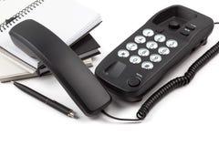 Aufgehobenes Telefon und Stapel Notizbücher auf weißem Hintergrund Lizenzfreies Stockbild