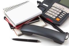 Aufgehobenes Telefon und Stapel Notizbücher auf weißem Hintergrund Stockfoto