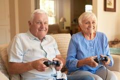Aufgeregte ältere Paare, die zusammen Videospiele zu Hause spielen Lizenzfreies Stockbild