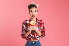Aufgeregte überraschte junge Stift-obenfrau, die Pommes-Frites hält stockfoto